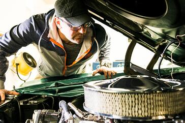 Automotive enthusiast looking at a vintage engine under the hood of a vehicle