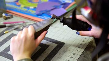 Cosplay maker sanding EVA foam with a dremel tool