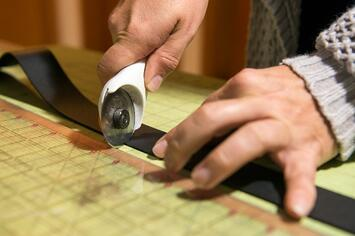 Jewelry maker cutting a leather strap for a cuff bracelet with a rotary cutter and a cutting mat