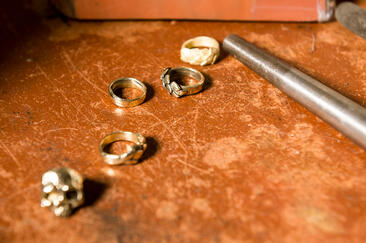 Metal wax cast jewelry laid out on a workbench with jewelry making tool