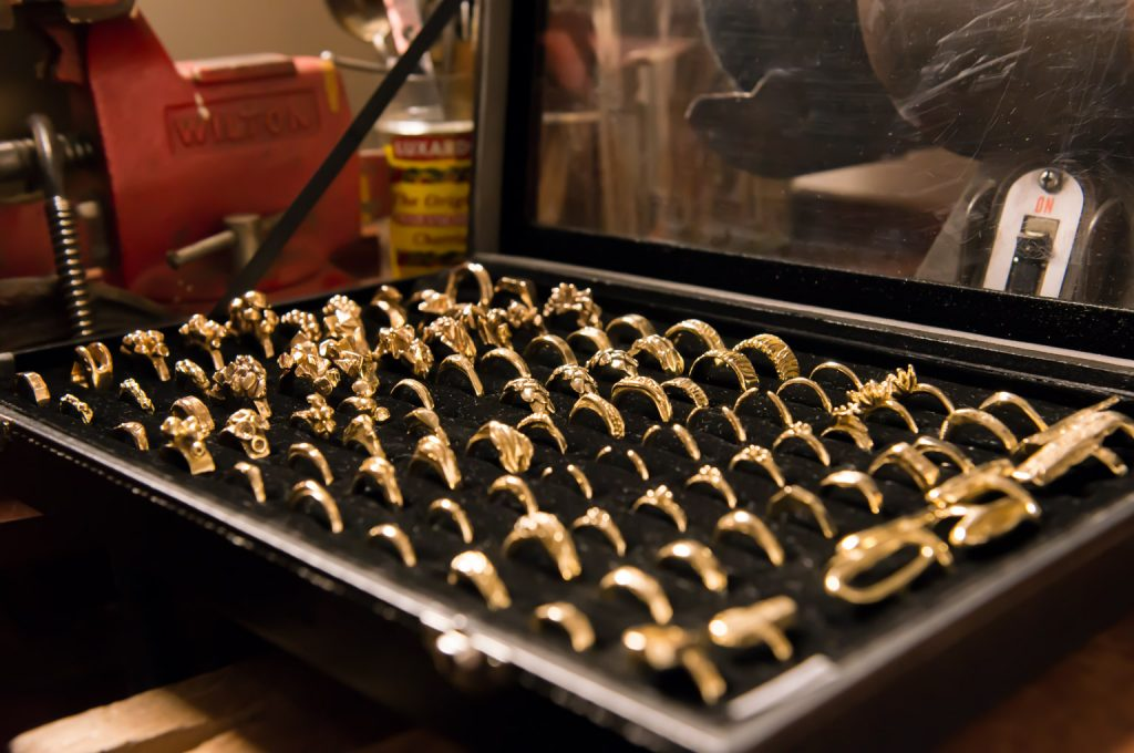 Display box full of gold rings created by jewelry maker using lost wax casting method
