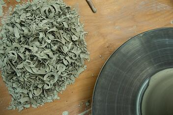 Clay shavings on a ceramicist's work table next to a pottery wheel