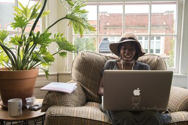 Smiling woman using Pinterest on a laptop in a maker studio in front of a window