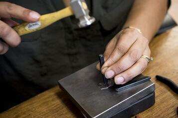 Jewelry maker stamping letters into a metal bar pendant