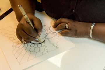 Paper crafter drawing a design on to a large card using a fine tip pen