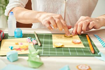 Paper crafter using craft tools and paper to create scrapbooking embellishments
