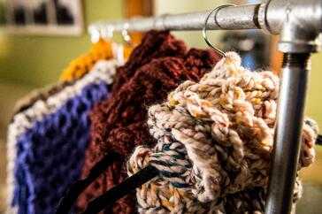 Knitted scarves in multiple colors hanging on a clothes rack