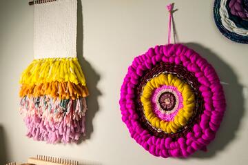 Finished yarn weavings made by a fiber artist hanging on a white wall