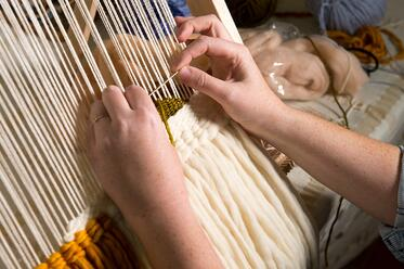 Weaver working on a loom weaving project using neutral yarn and a comb