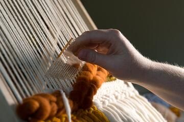 Fiber artist creating a weaving on a loom using a tutorial