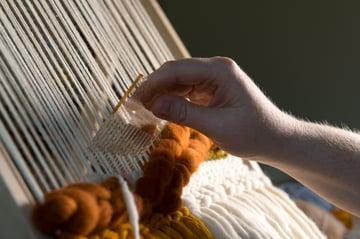 Fiber artist creating a weaving on a loom using a tutorial