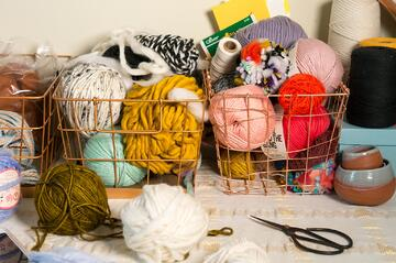 Fiber art supply basket filled with different colors and textures of yarn