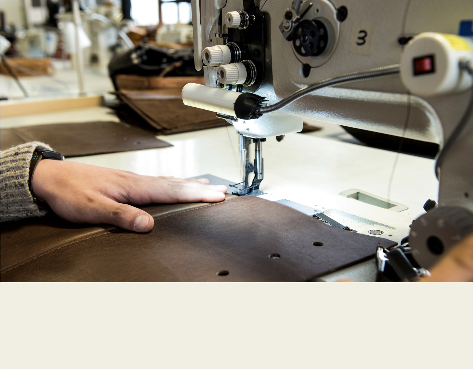 Maker who sews using a sewing machine on dark brown leather