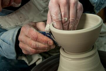 Ceramicist throwing a clay bowl on a pottery wheel