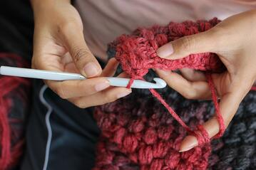 Fiber artist crocheting with red yarn and a hook
