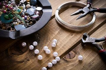 Jewlery making beads, wire, and supplies sitting on a wooden table