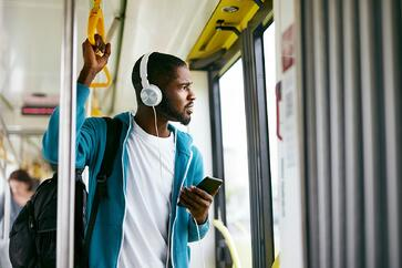 Man with headphones listening to a podcast on his phone during his bus commute