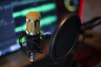 Podcast microphone recording episode to laptop with editing software