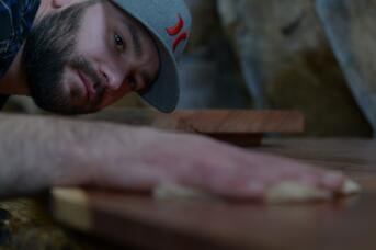 Woodworker demonstrating how to insert a slab into a planer