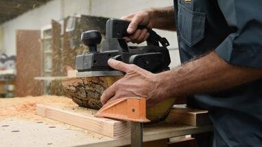 Woodworker using a power sander on an organic piece of wood