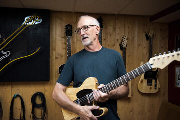 Modern luthier Dave Lackey holding his handmade electric guitar