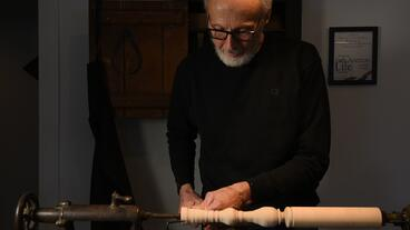 Master woodturner cutting a chair leg on a lathe