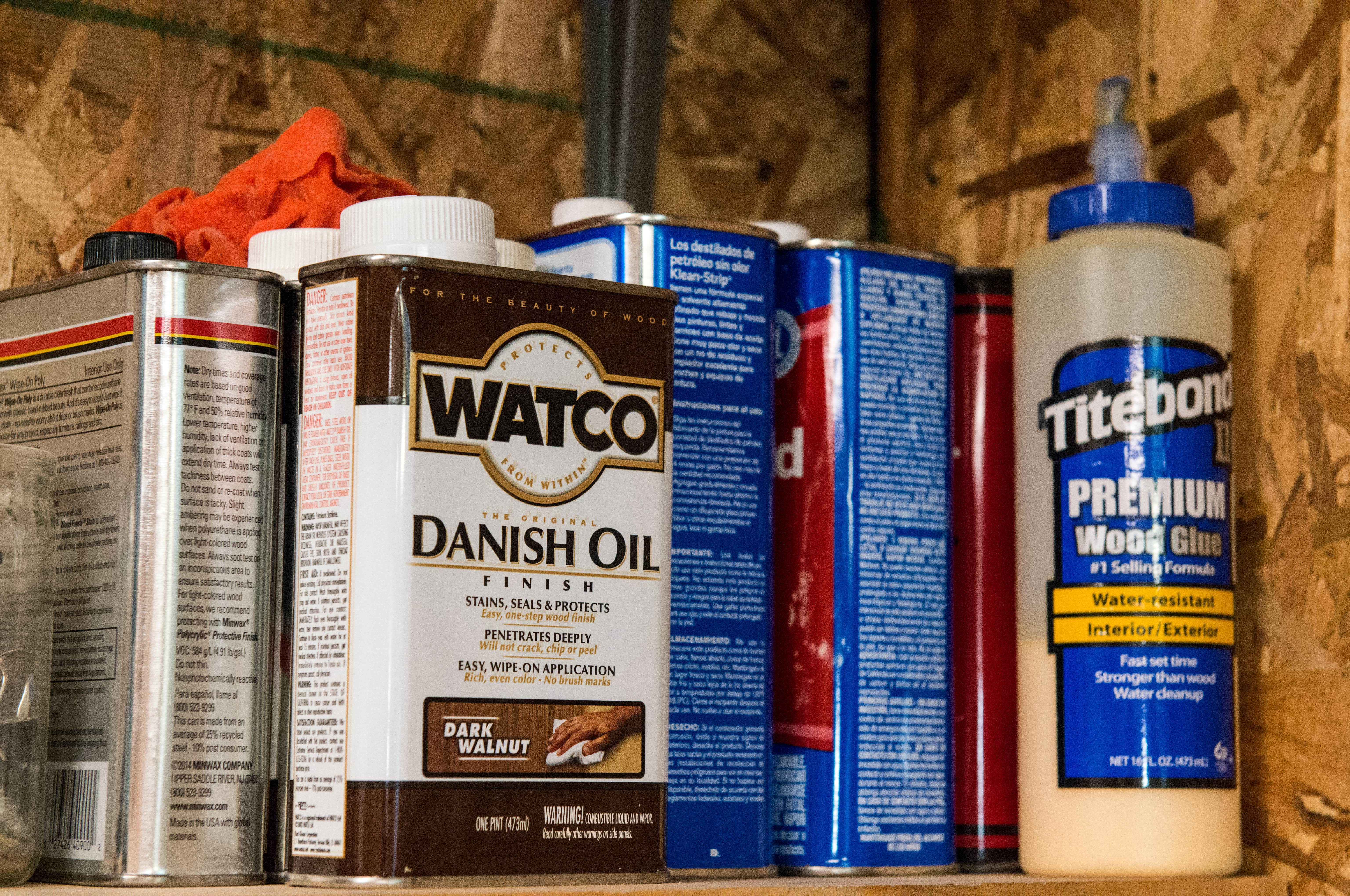 Wood oil and adhesive products that woodworkers use on a shelf in a workshop