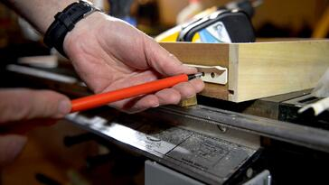 Woodworker demonstrating screwing a track into a dresser drawer