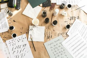 Calligraphy and hand lettering supplies and papers spread out on table