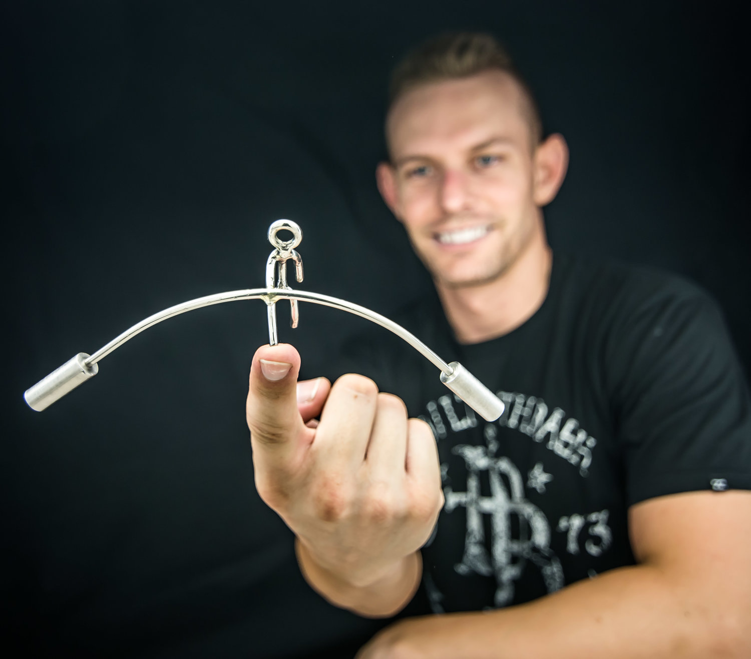 Kyle Auga of Kyle's Kinetics balances one of this metal sculptures on his finger