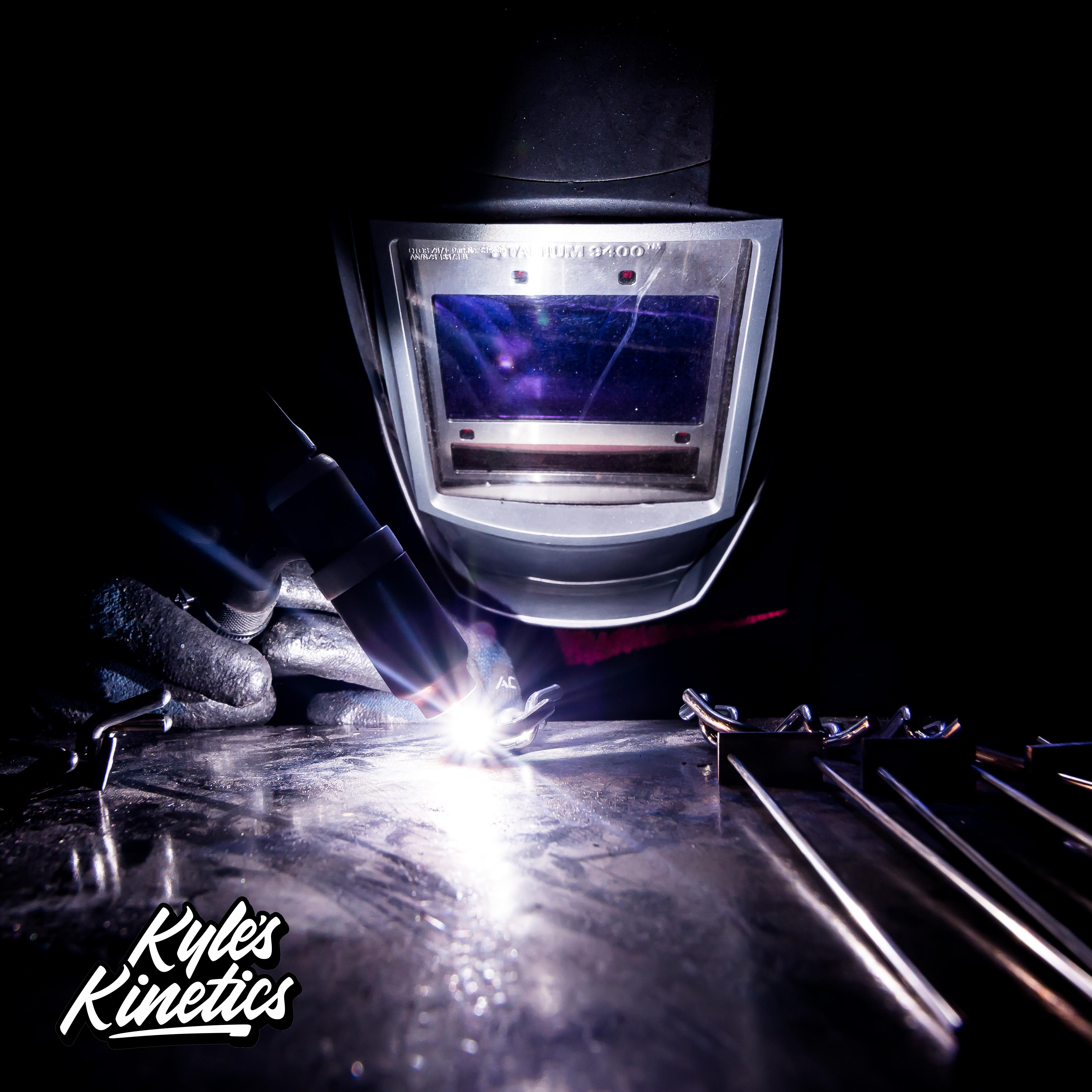 Kyle of Kyle's Kinetics welding stainless steel balancing sculptures in a welding mask